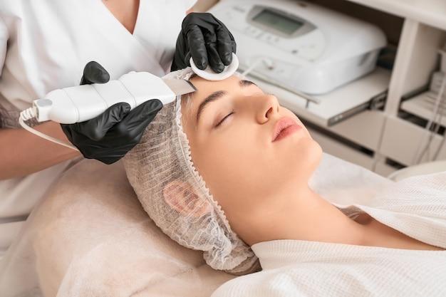 Woman undergoing procedure of facial peeling in beauty salon