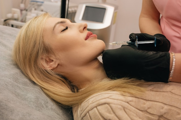 Женщина проходит процедуру изменения контура лица с помощью инъекций гиалуроновой кислоты. укол подбородка, концепция красоты.