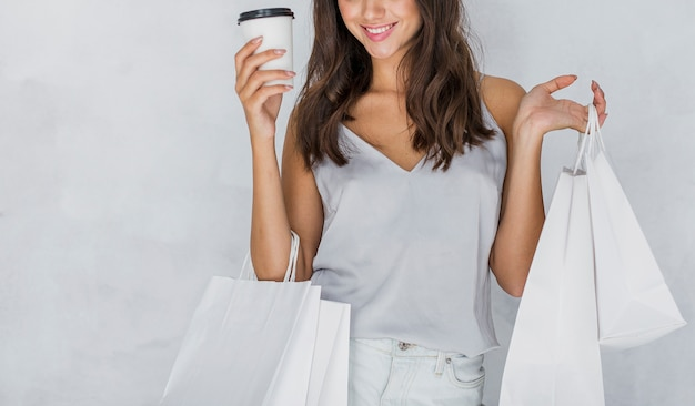 Woman in undershirt with shopping bags and coffee