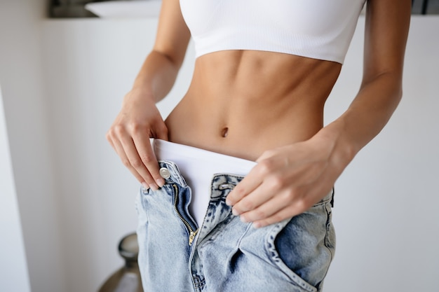 Woman undressing jeans and showing white underwear