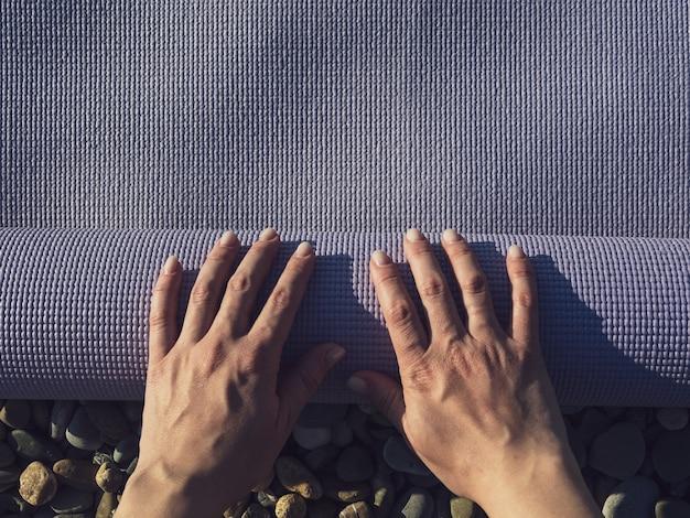 Женщина разворачивает коврик для йоги