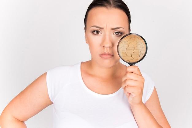 Женщина недовольна своей сухой поврежденной кожей, концепция красоты женственности ухода за кожей. женщина, держащая лупу к ее лицу.