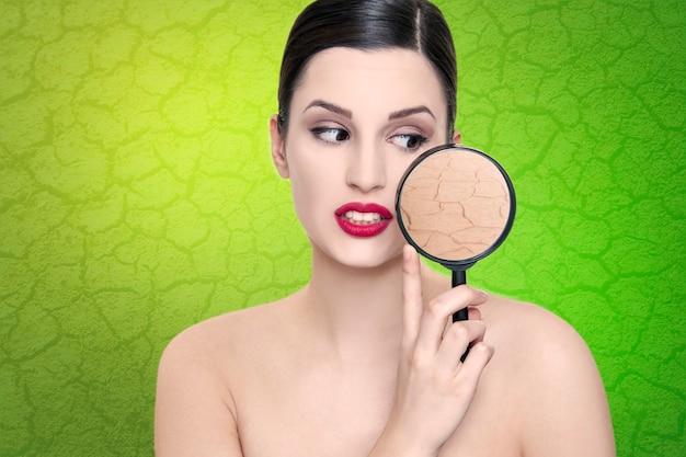 Женщина недовольна своей сухой кожей и увлажняющей концепцией ухода за кожей морщин. женщина держит лупу к лицу, показывая морщины