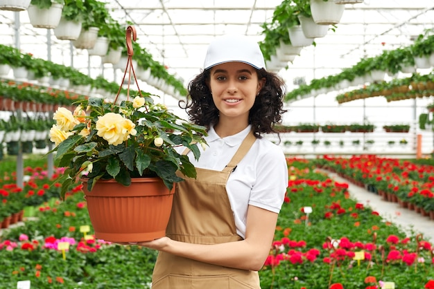 Woman in uniform posing at greenhouse with flower pot