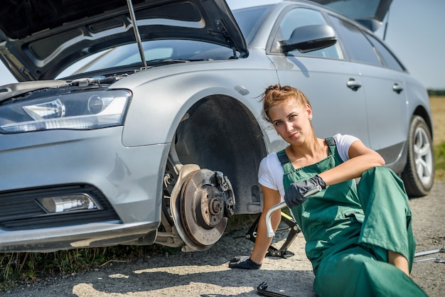 Woman in uniform working for car brake maintenance. car repair. safety work