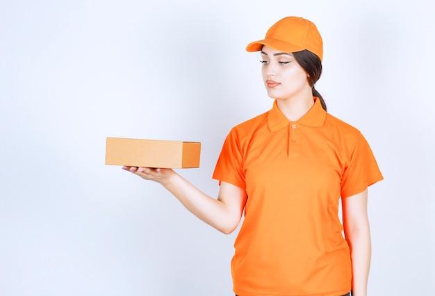 La donna in un'uniforme che tiene un pacco sul muro bianco