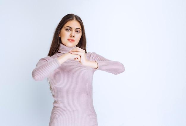 Donna che unisce le mani come un collegamento per mostrare dedizione.