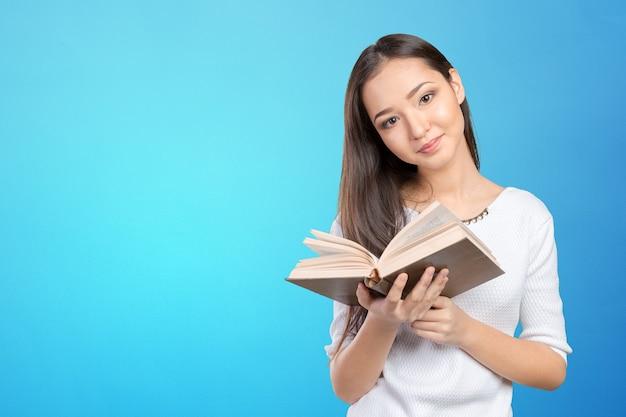 Студент университета / колледжа женщина держит книгу