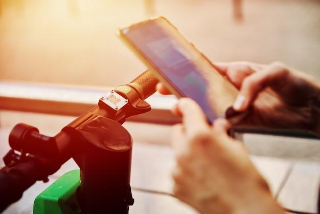 スマートフォンアプリで電動スクーターのロックを解除する女性