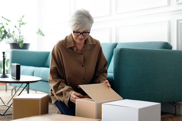 Donna che disimballa scatole marroni in soggiorno