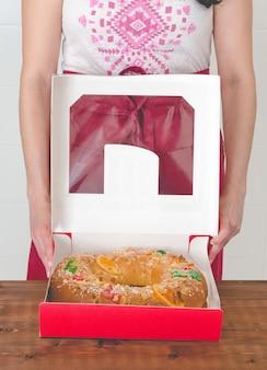 Женщина распаковывает короли торт.
