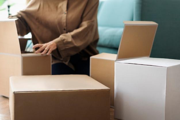Женщина распаковывает крафт-коробки в гостиной