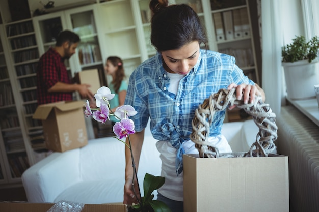 Woman unpackingcarton boxes while family standing in background