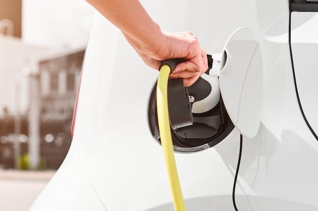 電気自動車のソケットから充電器を抜く女性。排出ガスゼロのエコカー