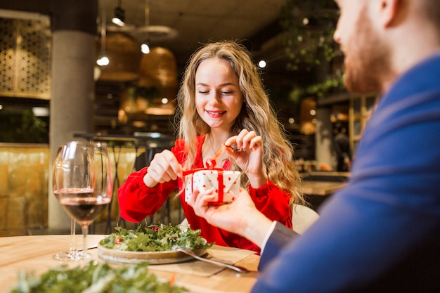 Woman untying bow on present from man