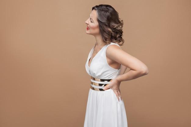 Женщина нездорова. боль в спине. концепция эмоций и чувств. студийный снимок, закрытый, изолированный на светло-коричневом фоне