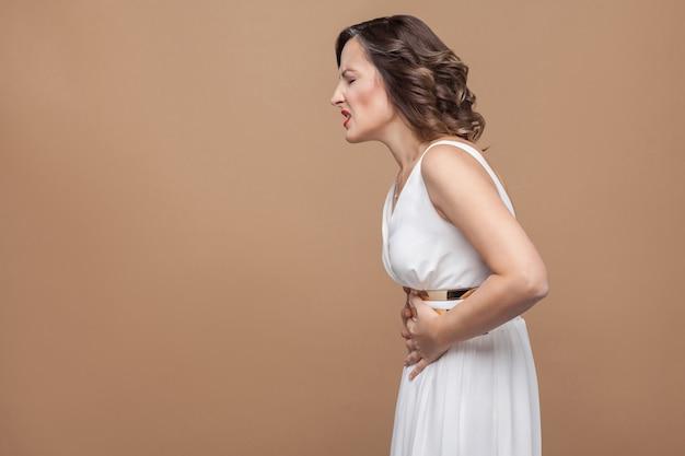 女性は具合が悪い。腹痛がある。感情と感情の概念。スタジオショット、屋内、薄茶色の背景に分離