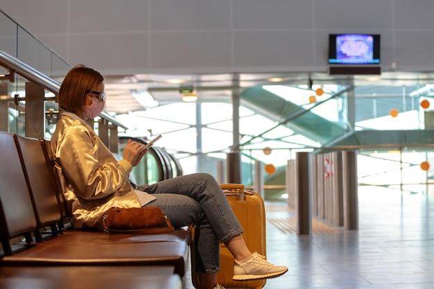 ほぼすべて空の空港ターミナルに座っているスマートフォンを使用して、フライトのキャンセルで動揺の女性