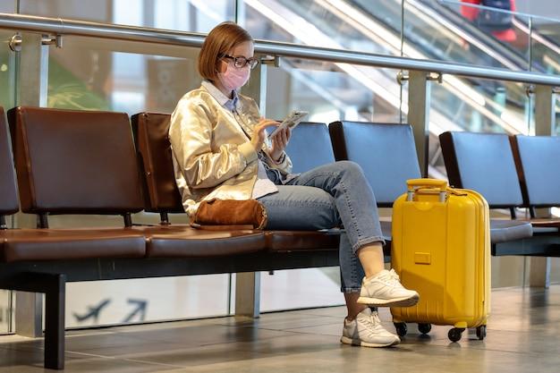 ほとんどの空の空港ターミナルに座っている女性がフライトのキャンセルに怒って、メッセージを書いている