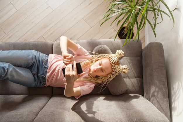 Женщина использует смартфон, лежа на диване. вид сверху. учеба онлайн, фрилансер.