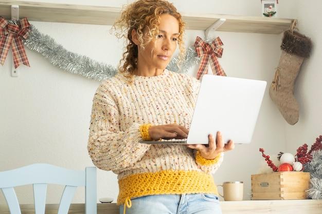女性は、バックグラウンドでクリスマスの装飾とコンピューターを使用します。