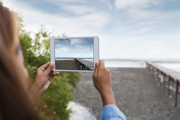Woman use digital tablet taking landscape photo