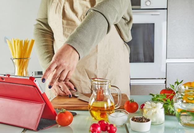 여자는 온라인 가상 마스터 클래스의 자습서에 따라 태블릿 화면 요리에 손가락 슬라이드를 사용합니다.