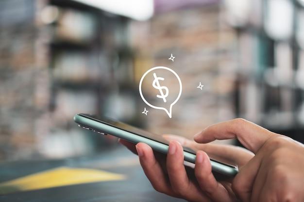 女性はガジェットモバイルスマートフォンを使用して、ドルアイコンがポップアップしてオンラインでお金を稼ぎます。スマートフォンのコンセプトに関するビジネスフィンテックテクノロジー。