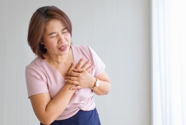 女性は手を使って胸に痛みを感じ、心臓病に苦しんでいます。コピースペースを備えたst上昇型心筋梗塞の概念。