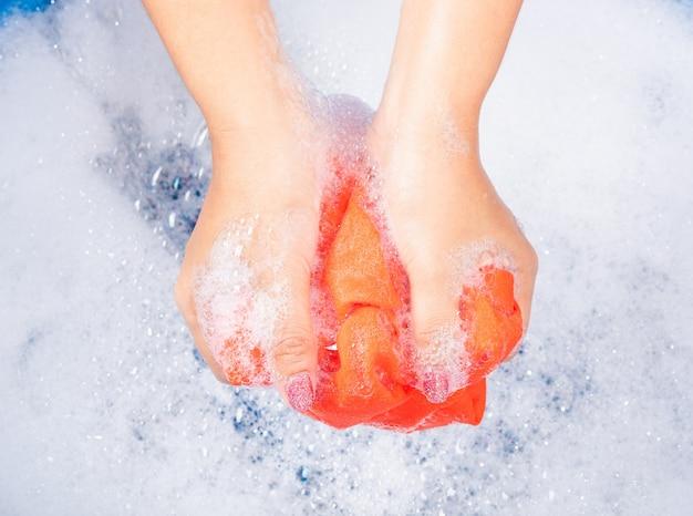 Woman use hands washing color clothes in basin with detergent have soapy bubble water