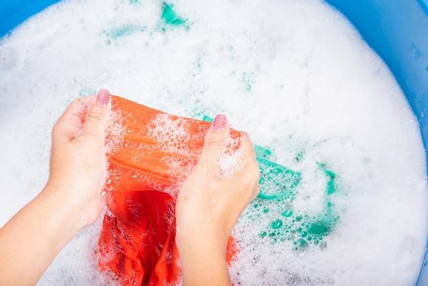 Женщина руками стирает цветную одежду в тазу с моющим средством с мыльной водой с мыльными пузырями