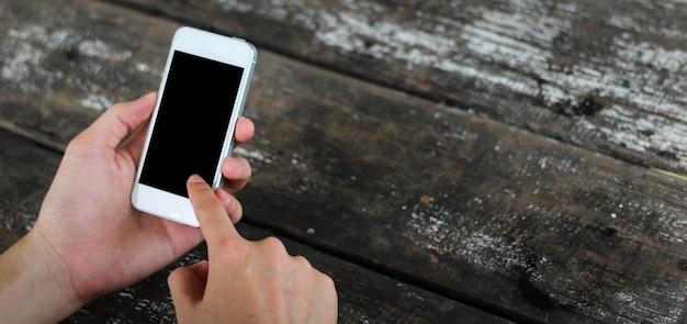 Женщина использует мобильный телефон в кафе