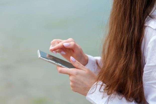 여자는 휴대 전화를 사용하여 외부의 인터넷 확인 앱에서 검색합니다. 긴 머리를 가진 여자 스마트폰으로 근접 촬영 여성 손 바다 물 표면 배경에서 나머지. 여행에서 여자 문자 메시지입니다.