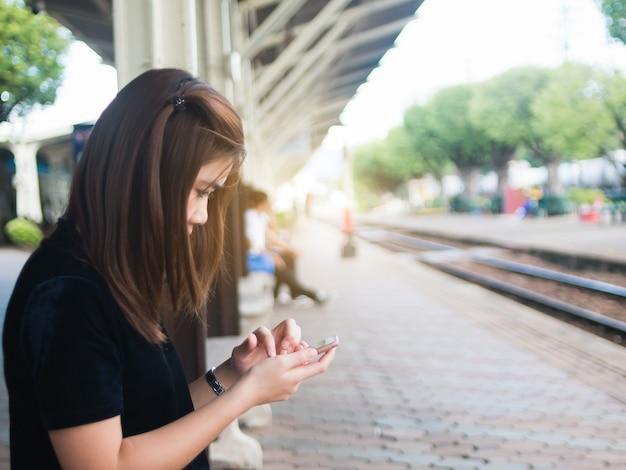 Woman use of mobile phone at the trains station