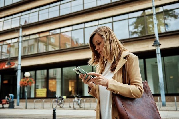 여자는 도시 거리에서 스마트폰을 사용