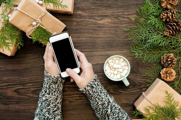 Женщина использовать смартфон с copyspace на дереве