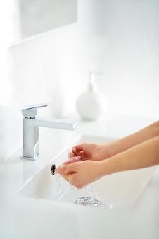 女性は石鹸を使い、水道の蛇口の下で手を洗います。衛生コンセプトの手の詳細。