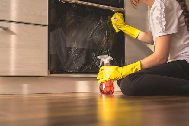 여자는 나무 바닥에 앉아 있는 주방 오븐을 청소하기 위해 스프레이 세제를 사용한다