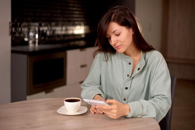 Женщина использует планшет дома с чашкой кофе или чая на кухне