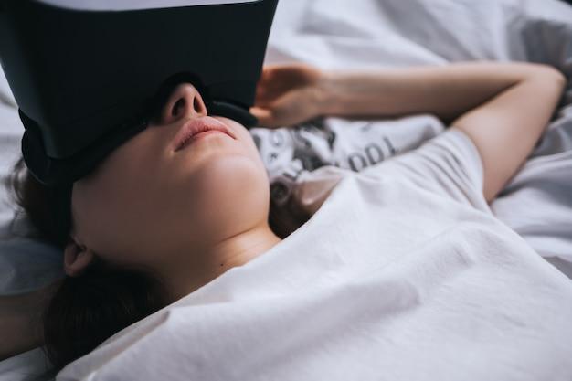 女性は自宅でバーチャルリアリティメガネを使用し、ベッドでリラックスしています。ゲーム、未来のテクノロジーをプレイする