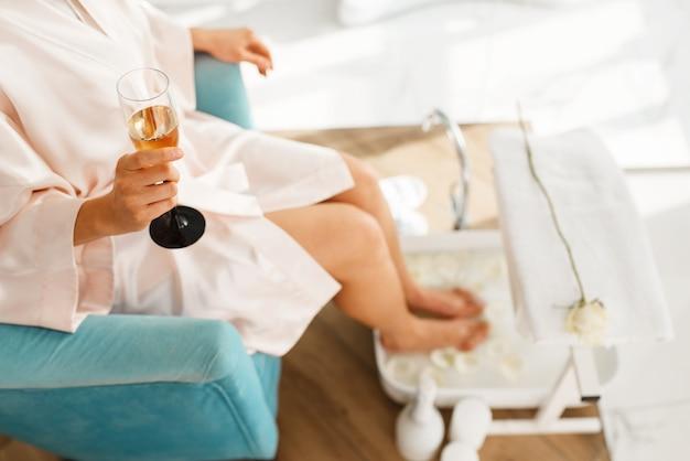 여자는 발 목욕을 사용하고 샴페인을 마신다.