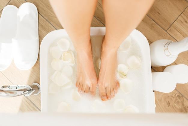 여자는 흰색 장미 꽃잎, 미용실과 발 목욕을 사용합니다.
