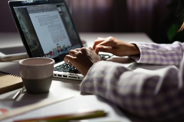여성은 늦은 저녁에 새로운 프로젝트 아이디어를 작업하는 동안 노트북을 사용합니다. 여성의 손이 노트북 키보드에 입력하고 있습니다