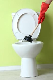 여자는 플런저를 사용하여 화장실에서 변기의 막힘을 풀다