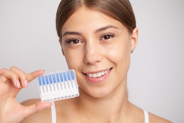 The woman uses brushes to clean the interdental spaces.