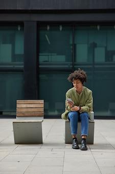 女性はセルラーアプリケーションを使用しますスマートフォンでメッセージを送信します公共のwifiに接続されたインターネットを使用しますスタイリッシュな服を着ています屋外に座って何かを待ちます