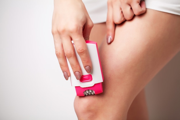 Woman uses epilator to remove hair on legs in bathroom in home apartment