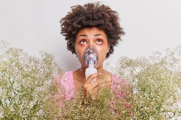 女性は吸入器ネブライザーを使用しており、野生の花にアレルギーがあることを呼吸するのに役立ちます。白のポーズの上に焦点を当てたアレルゲンへの反応として、目が赤く腫れています。