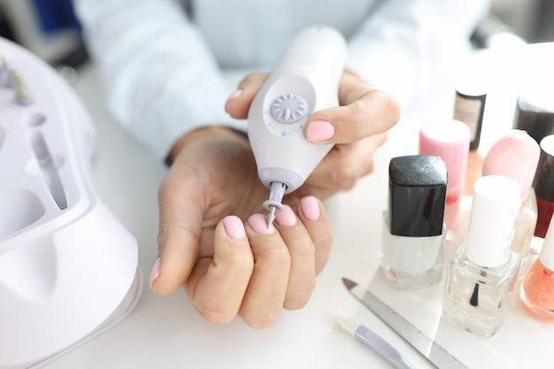 여자는 매니큐어 기계를 사용하여 손톱 홈 매니큐어 개념을 치료합니다