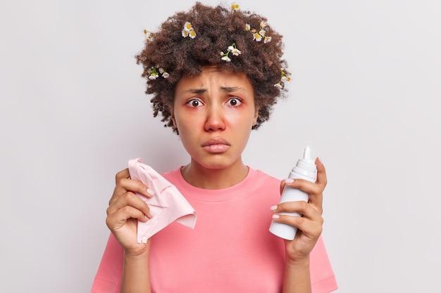 여성은 비강 에어로졸을 사용하여 알레르기성 비염으로 고통받고 있습니다. 빨간색으로 부어오른 눈은 흰색 위에 격리된 캐주얼 티셔츠를 입은 불행해 보입니다.